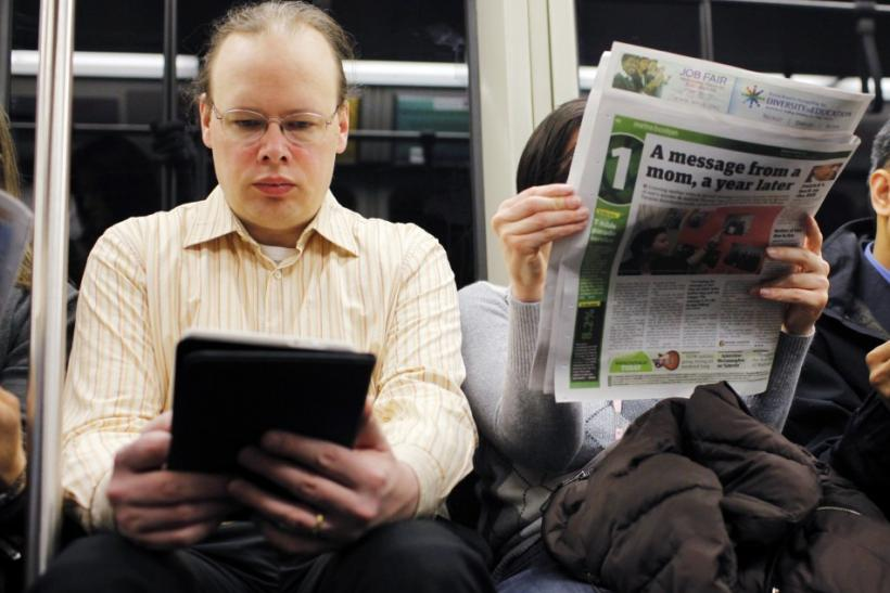 A commuter reads on a Kindle e-reader while riding the subway in Cambridge, Massachusetts