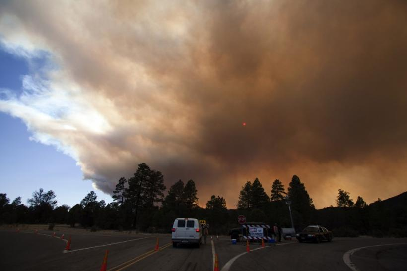 Smoke from the Wallow Wildfire obscures the sun at a road check point west of the Reserve, New Mexico