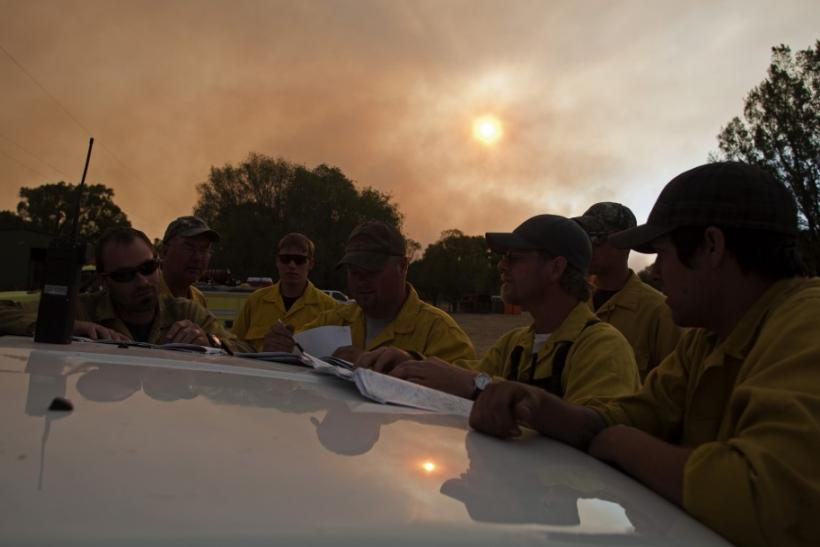 Wildland firefighters go over maps of the Wallow Wildfire as the sun sets in Luna, New Mexico