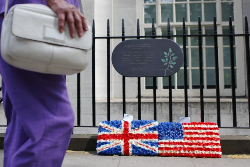 A pedestrian passes wreaths placed under a plaque commemorating the victims of the July 7 London bombing in Tavistock Square, in central London