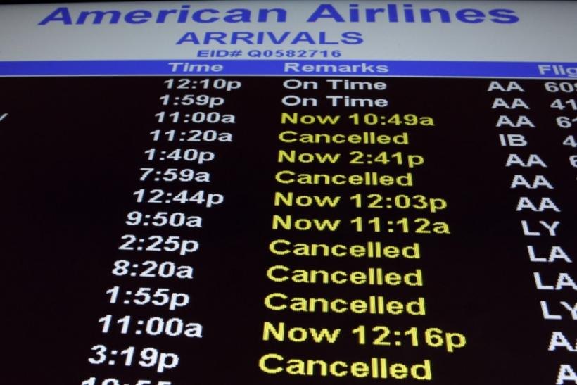An arrivals board for American Airlines displays cancelled and delayed flights at the John F. Kennedy International Airport in New York