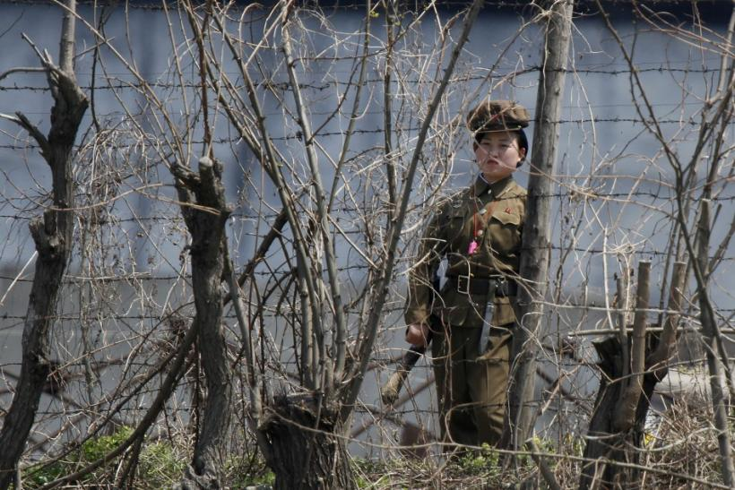 A North Korean prison policewoman stands guard behind fences at a jail on the banks of Yalu River near the Chongsong county of North Korea
