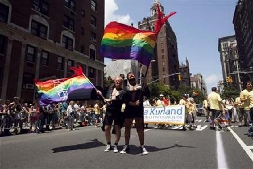 Men dressed in tuxedo jackets to emulate grooms at a wedding wave flags touting their 30 years in a relationship together as a form of support for gay marriage, in the annual Gay Pride Parade in New York June 28, 2009.