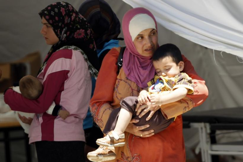 Syrian women wait for medical assistance for their children at a refugee camp in Yayladagi in Hatay province