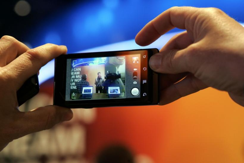 A man takes a photo with a Motorola Milestone smartphone during the 2010 International CES in Las Vegas
