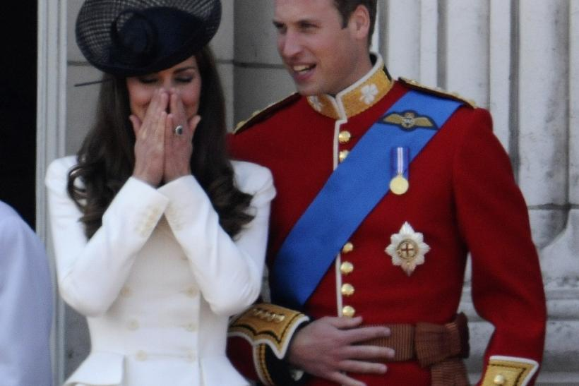 Britain's Prince William and his wife Catherine, Duchess of Cambridge, share a light moment on the balcony of Buckingham Palace after attending the Trooping the Colour ceremony in central London