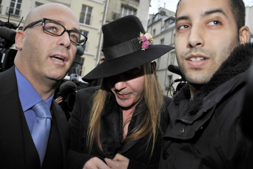 Fashion designer Galliano and his lawyer Zerbib arrive for a hearing at a police station in Paris