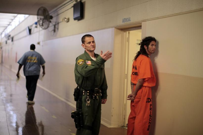 An inmate is led by a prison guard at the California Institution for Men state prison in Chino