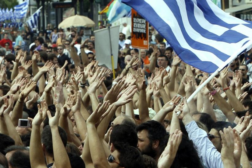 Demonstrators wave flags near the Greek parliament in Athens