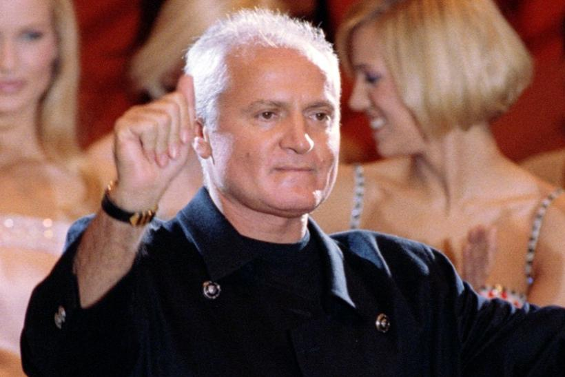 Italian designer Gianni Versace greets the audience as the models applaud following the presentation..