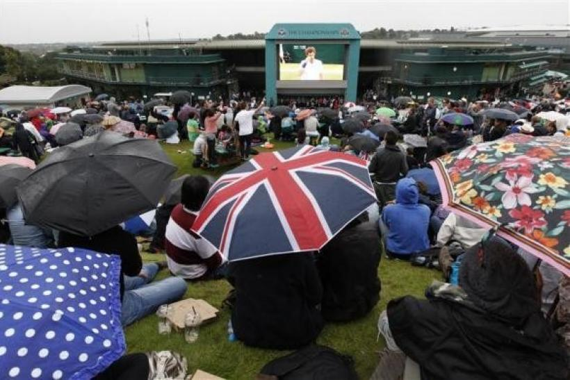 Spectators hold umbrellas as they sit on Murray's Mount