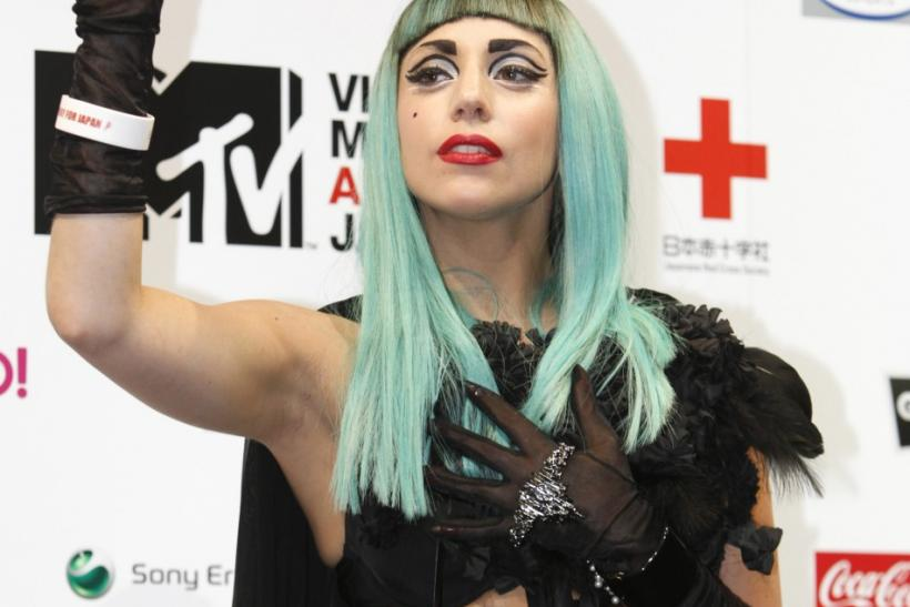 Lady Gaga waves during a news conference in Tokyo