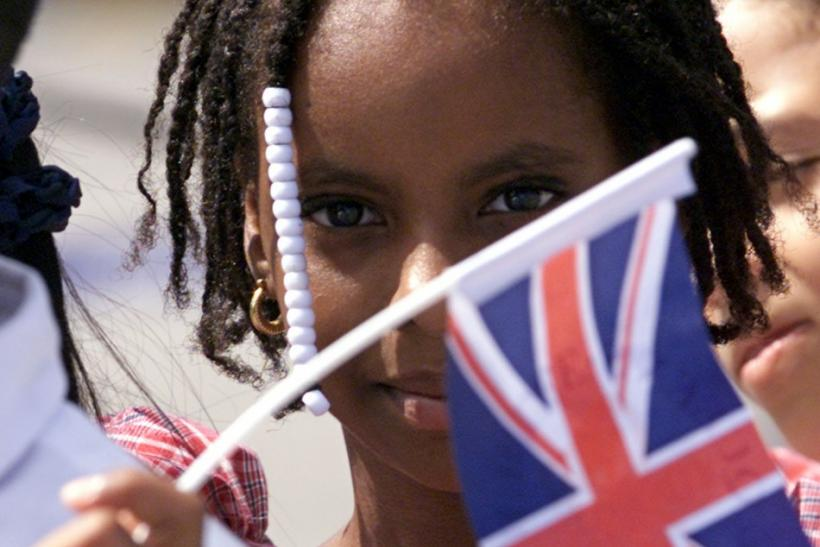 Jamaican children wave flags as they await [Britain's Queen Elizabeth] at Montego Bay's Airport,