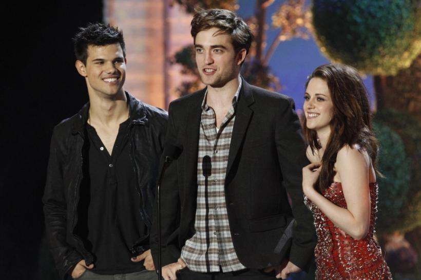 """Taylor Lautner (L), Robert Pattinson and Kristen Stewart introduce a clip from """"The Twilight Saga: Breaking Dawn"""" at the 2011 MTV Movie Awards in Los Angeles, June 5, 2011."""