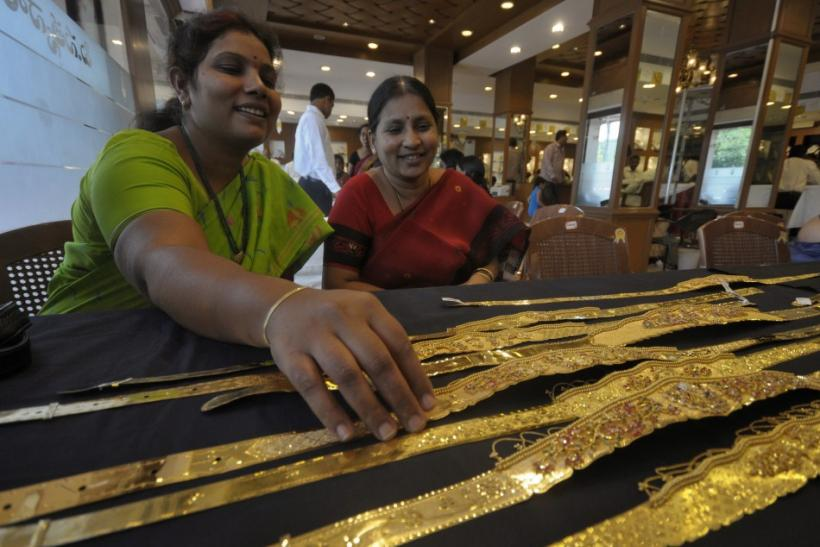 A woman checks a gold waist belt inside a jewellery shop on the occasion of Akshaya Tritiya festival in Hyderabad