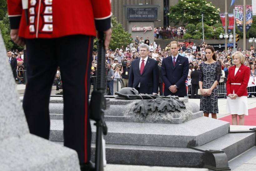 Canada's Prime Minister Harper and wife Laureen stand in silence alongside Britain's Prince William and wife Catherine, Duchess of Cambridge at the National War Memorial in Ottawa