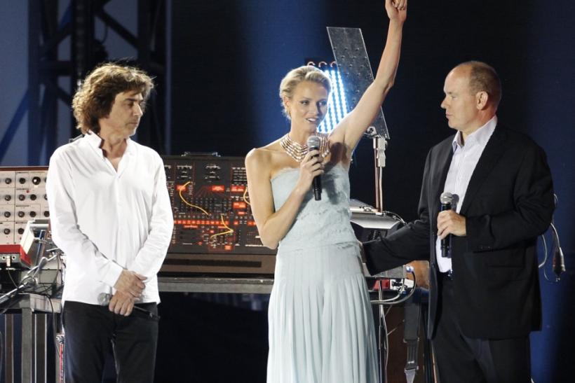 Monaco's Prince Albert II and his wife Princess Charlene stand with French composer and musician Jean-Michel Jarre before his concert in the Harbour of Monaco