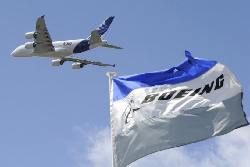 Boeing flags flutter as an Airbus A380, the world's largest jetliner, takes part in a flying display during the 49th Paris Air Show at the Le Bourget airport near Paris