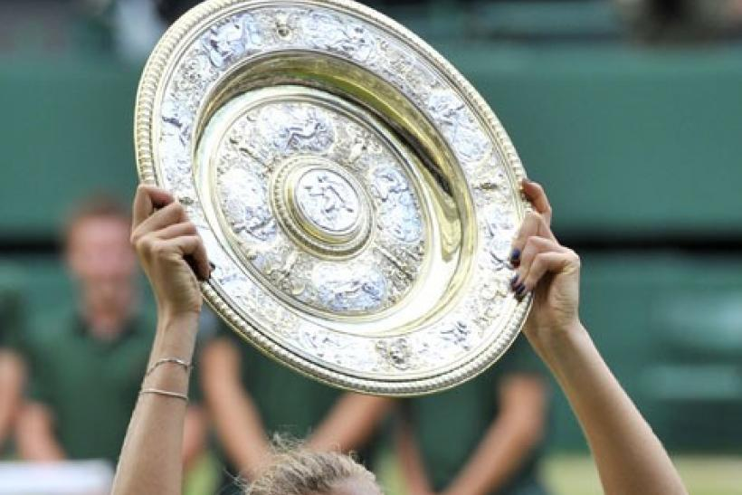 Petra Kvitova of the Czech Republic holds the winners trophy after defeating Maria Sharapova
