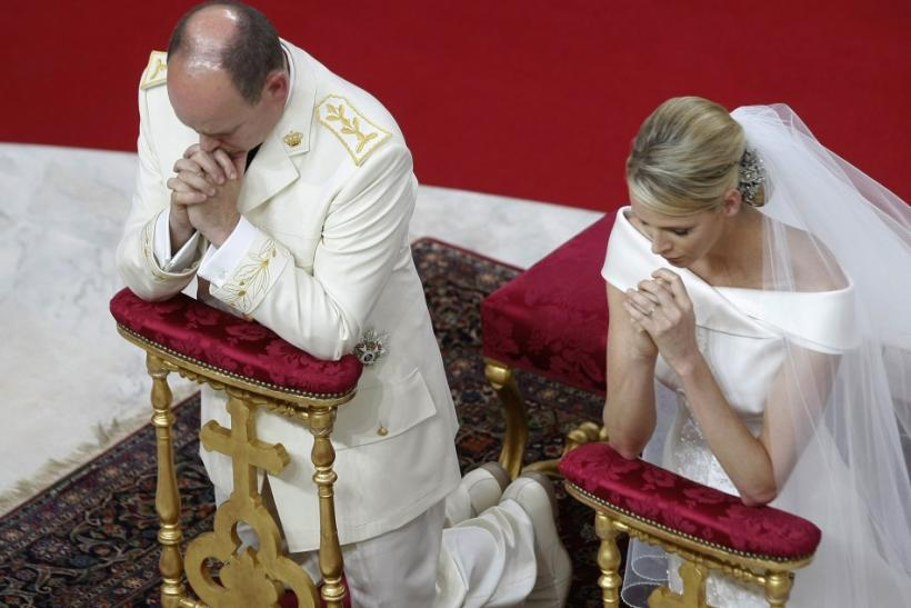 Monaco's Prince Albert II and Princess Charlene kneel at the altar during their religious wedding ceremony in Monaco