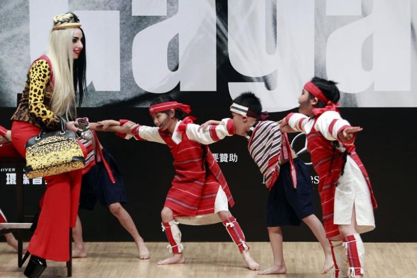 U.S. singer Lady Gaga watches children from the traditional Taiwan aborigine Taiya tribe dance