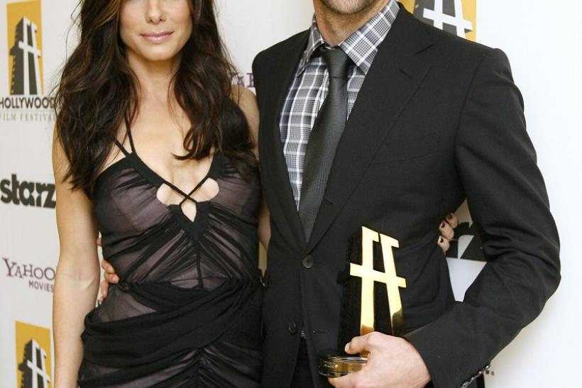 Actor Bradley Cooper (R) poses with actress and presenter Sandra Bullock