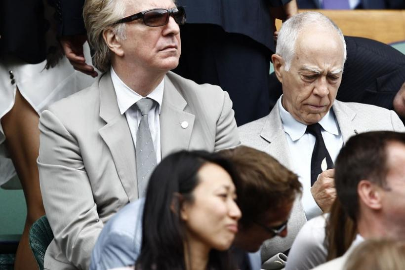 Actor Alan Rickman (L) sits on Centre Court during the men's singles final match