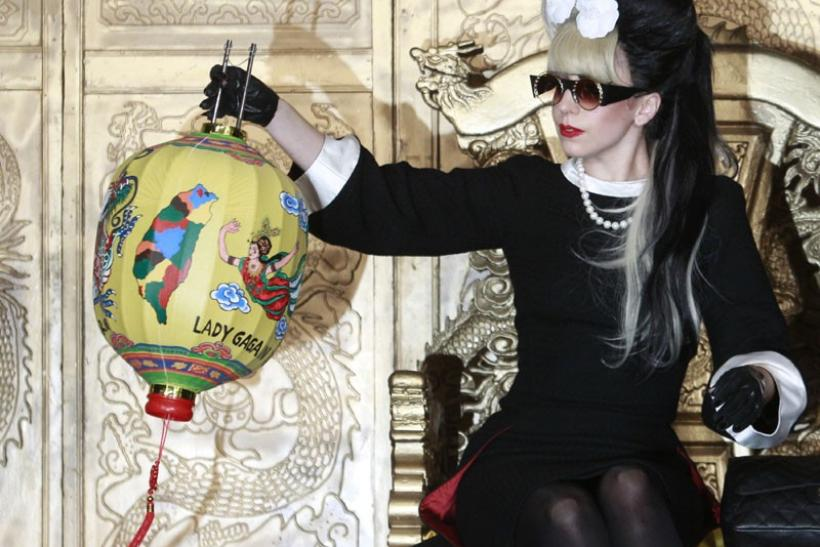Lady Gaga looks at a Chinese lantern presented to her