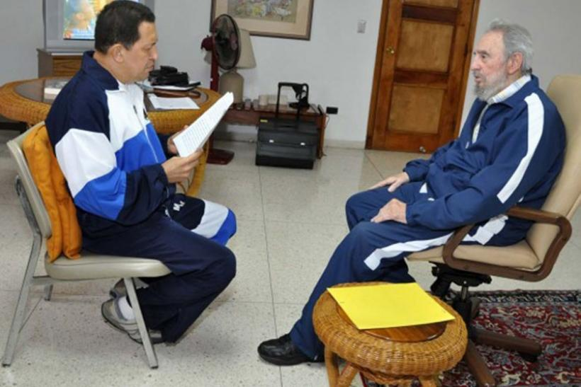 Cuban leader Fidel Castro looking on as Venezuela's President Hugo Chavez reads a document