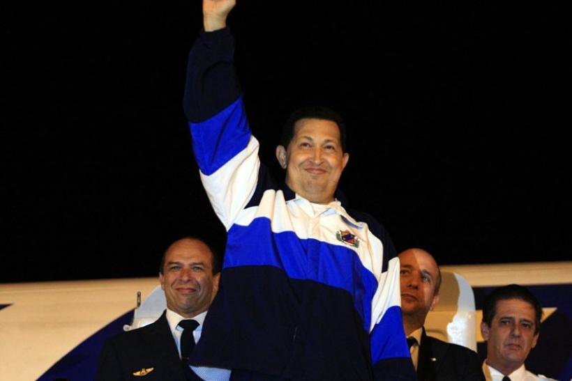 Venezuela's President Hugo Chavez gestures from the doorway of a plane upon arrival from Cuba
