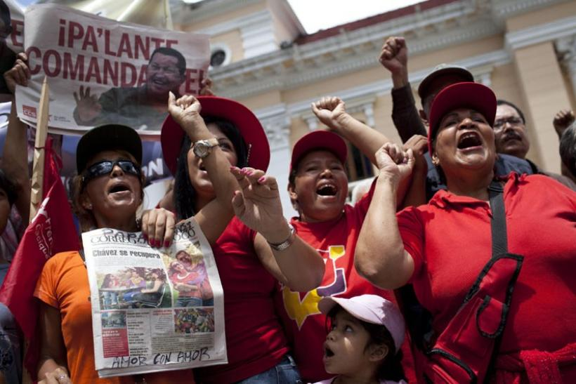 Supporters of Venezuelan President Hugo Chavez hold newspapers with a picture of him