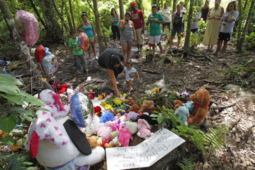 Neighbors gather at the wooded location of where the body of Caylee Anthony was found