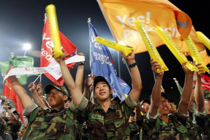 South Korean Army soldiers cheer as they hear that Pyeongchang would win in a first round of voting for the 2018 Winter