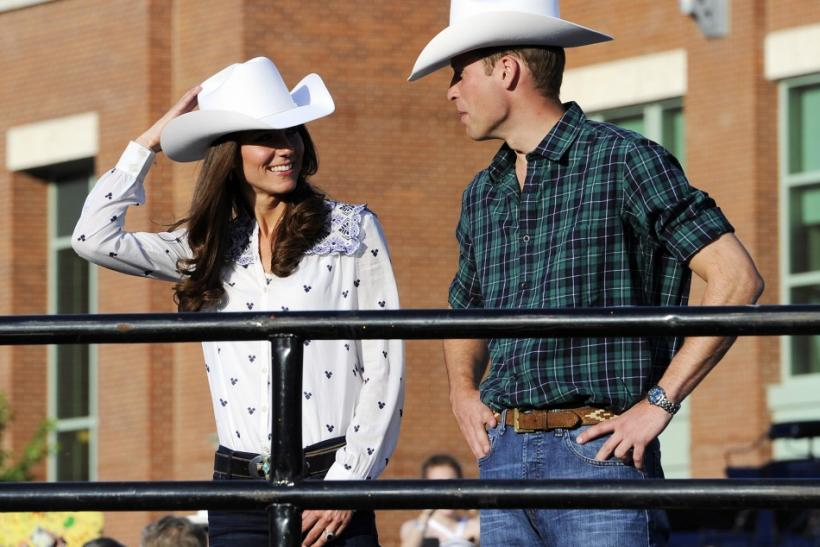 Britain's Prince William talks to his wife Catherine, Duchess of Cambridge, during a tour of the Calgary Stampede