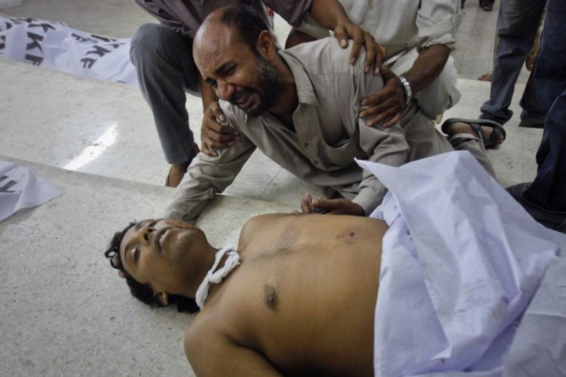 A family member of a victim of a target killing cries next to his body at a morgue in Karachi's Abbasi Shaheed hospital