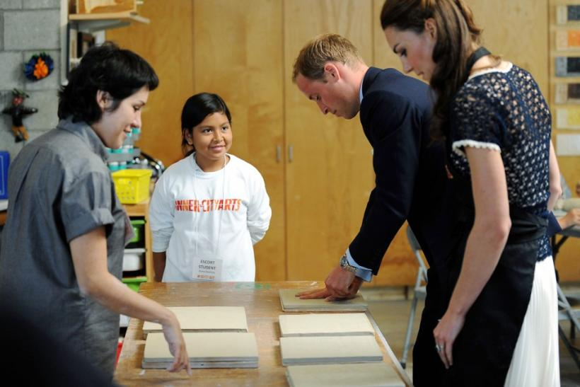 Britain's Prince William and his wife Catherine, Duchess of Cambridge, make handprints in pieces of clay as a student and teacher Carmen Argote (L) looks on during their visit to the Inner-City Arts campus in Los Angeles, California