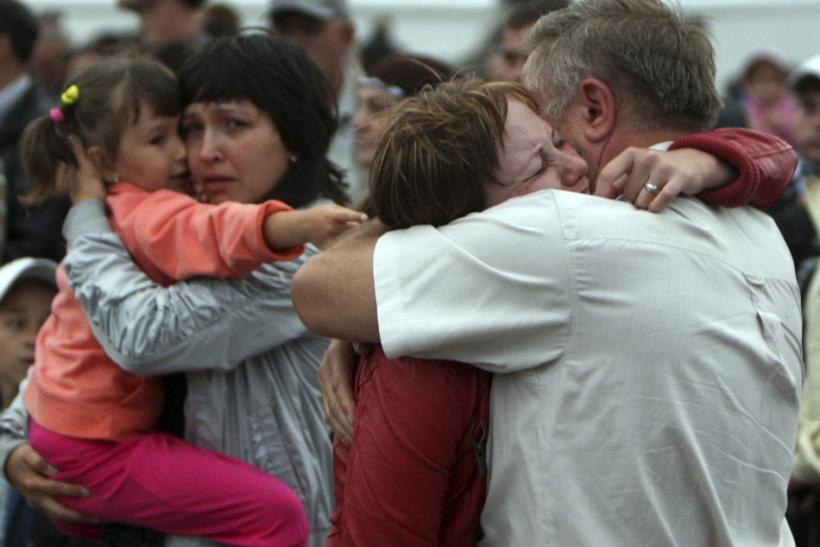 People react as they meet the survivors from the Bulgaria tourist boat, which sank on the Volga river, at the port of Kazan