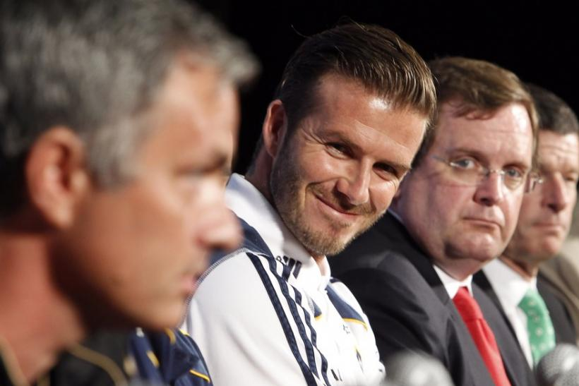 LA Galaxy's Beckham listens to Real Madrid head coach Mourinho at a news conference to announce the Herbalife World Football Challenge 2011