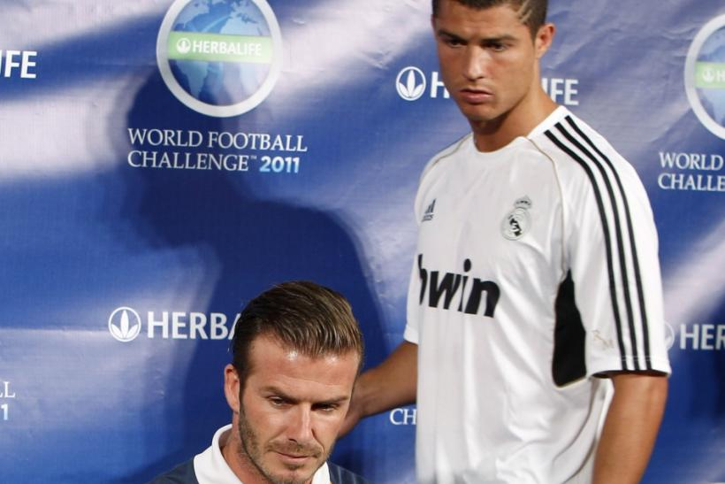 LA Galaxy's Beckham sits down as Real Madrid's Ronaldo looks for his seat at a news conference in Los Angeles
