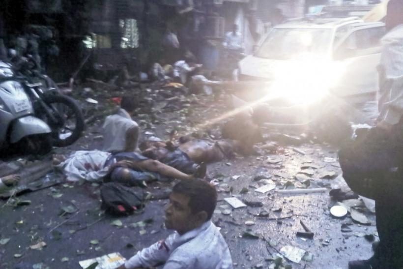 In this photo taken with a mobile phone, injured people lie on a street at the site of an explosion near the Opera House in Mumbai