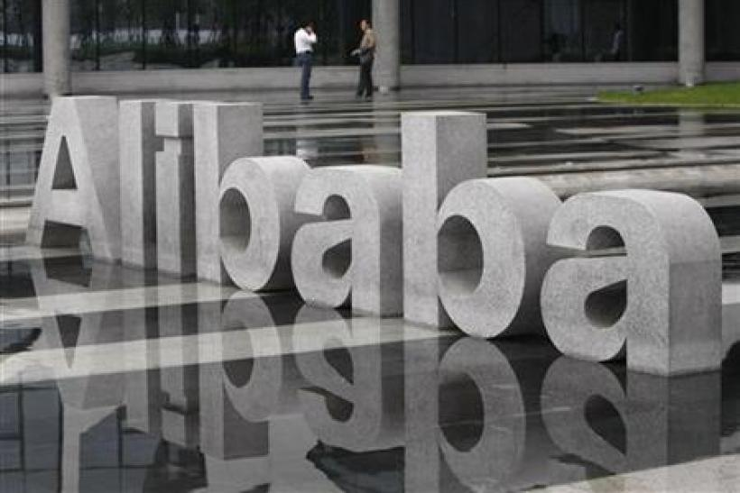 Two men chat beside a logo of Alibaba (China) Technology Co. Ltd at its headquarters on the outskirts of Hangzhou
