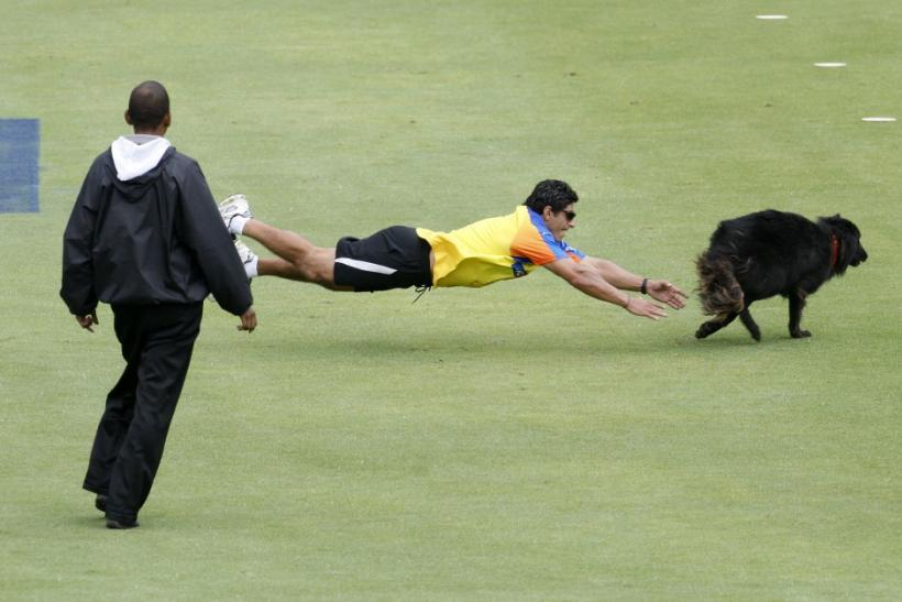 An official attempts to catch a dog that disrupted play in the opening game of IPL T20 cricket tournament between the Mumbai Indians and Chennai Super Kings in Cape Town