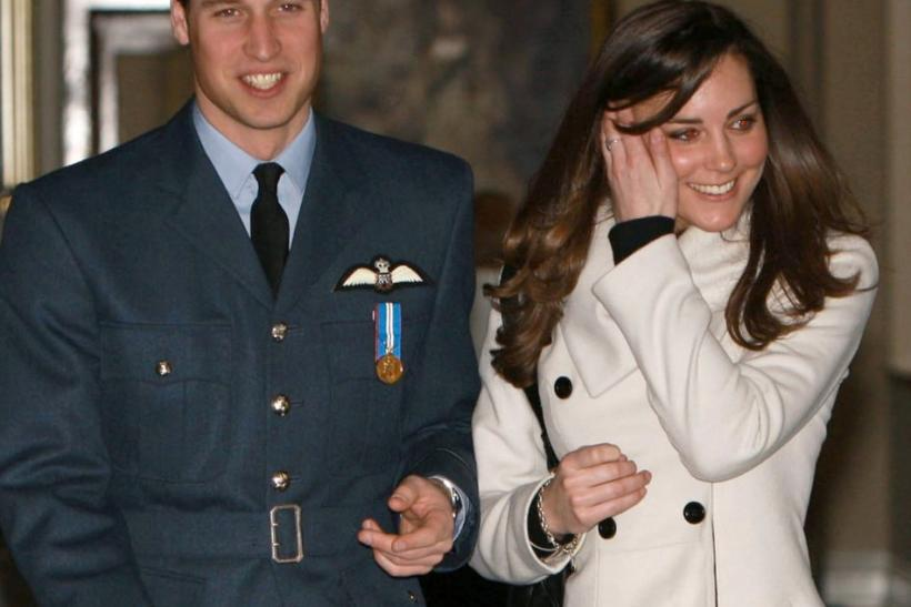 File photograph shows Britain's Prince William smilling as he walks with his girlfriend Kate Middleton at RAF Cranwell, central England