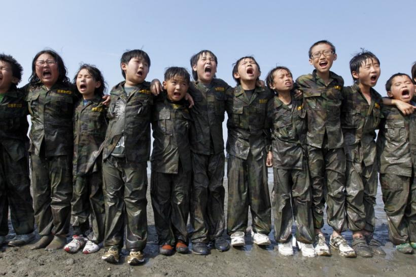 "Elementary school students shout ""Thanks to my parents!"" at a mud flat as they participate in a summer military camp for civilians at the Cheongryong Self-denial Training Camp run by retired marines in Ansan"