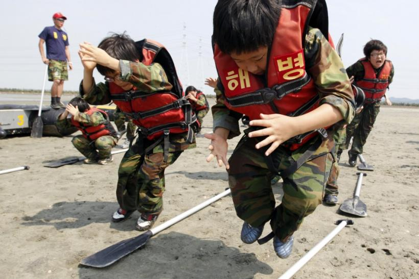 Elementary school students jump over paddles as they participate in a summer military camp for civilians at the Cheongryong Self-denial Training Camp run by retired marines in Ansan