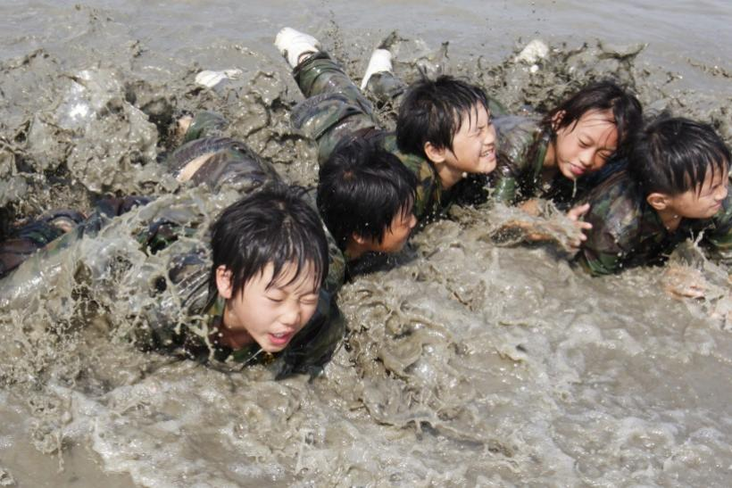 Elementary school students crawl forward at a mud flat as they participate in a summer military camp for civilians at the Cheongryong Self-denial Training Camp run by retired marines in Ansan