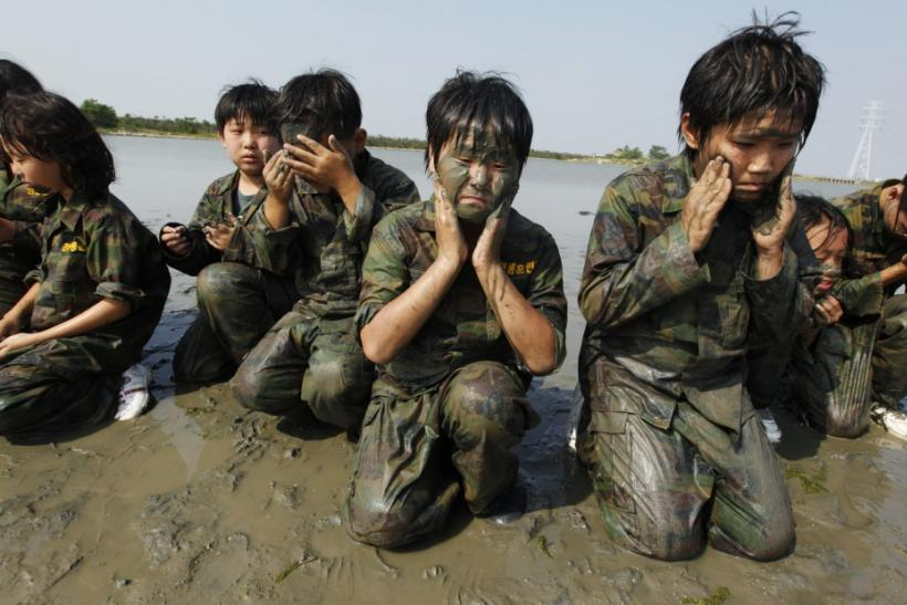Elementary school students apply mud on their faces as they participate in a summer military camp at the Cheongryong Self-denial Training Camp in Ansan