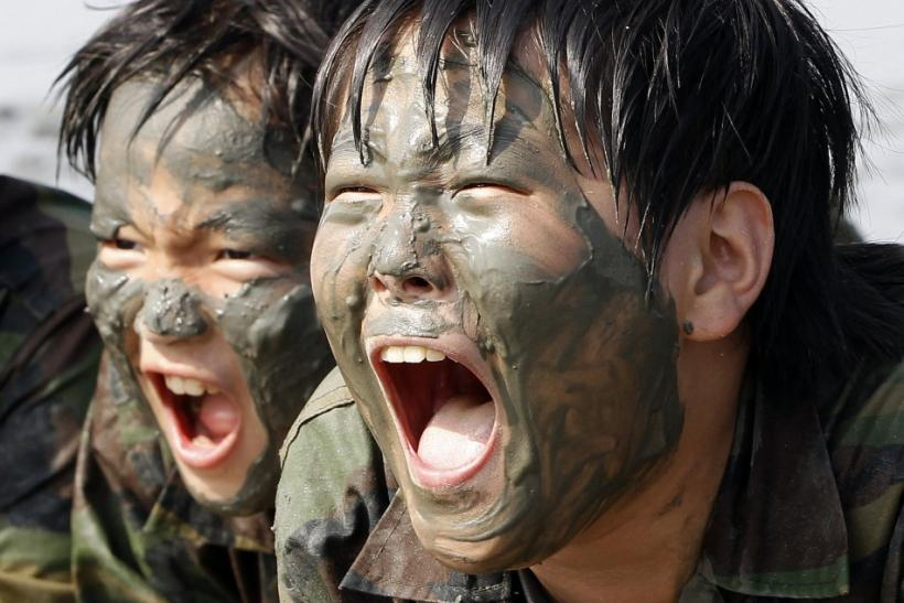 Elementary school students scream at a mud flat as they participate in a summer military camp for civilians at the Cheongryong Self-denial Training Camp run by retired marines in Ansan
