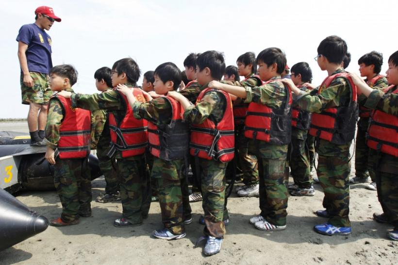 A camp instructor briefs elementary school students during a summer military camp for civilians at the Cheongryong Self-denial Training Camp in Ansan
