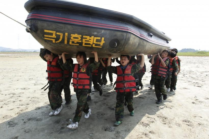 Elementary school students carry a rubber boat as they participate in a summer military camp at the Cheongryong Self-denial Training Camp in Ansan